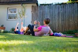 A mother and her kids do some home gym workouts together. Being fit and active at home during the Corona Virus lockdown period