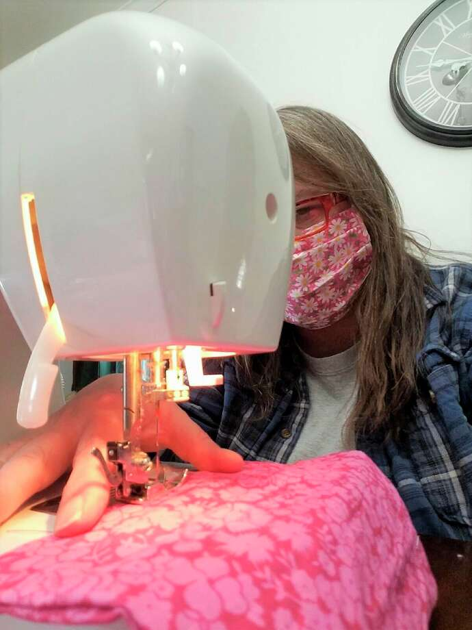 Pictured is Sharon Miller, sewing one of her face masks. She has sewn and donated more than 150 masks to local healthcare workers. (Courtesy photo)