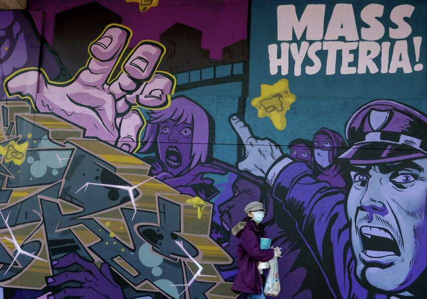 A pedestrian, wearing a protective mask, walks past a street art mural, depicting