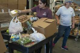 Anabel Gutierrez and Patti Edgar organize food bundles 04/15/2020 at the West Texas Food Bank in Midland for individuals and families to pick-up. Tim Fischer/Reporter-Telegram