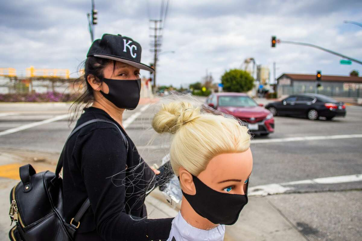 Dressmaker Flor Hernandez sells face masks on street after losing her job, during the novel coronavirus (COVID-19) outbreak, in Los Angeles on April 2, 2020. Los Angeles County has made wearing masks mandatory for anyone entering an essential business.