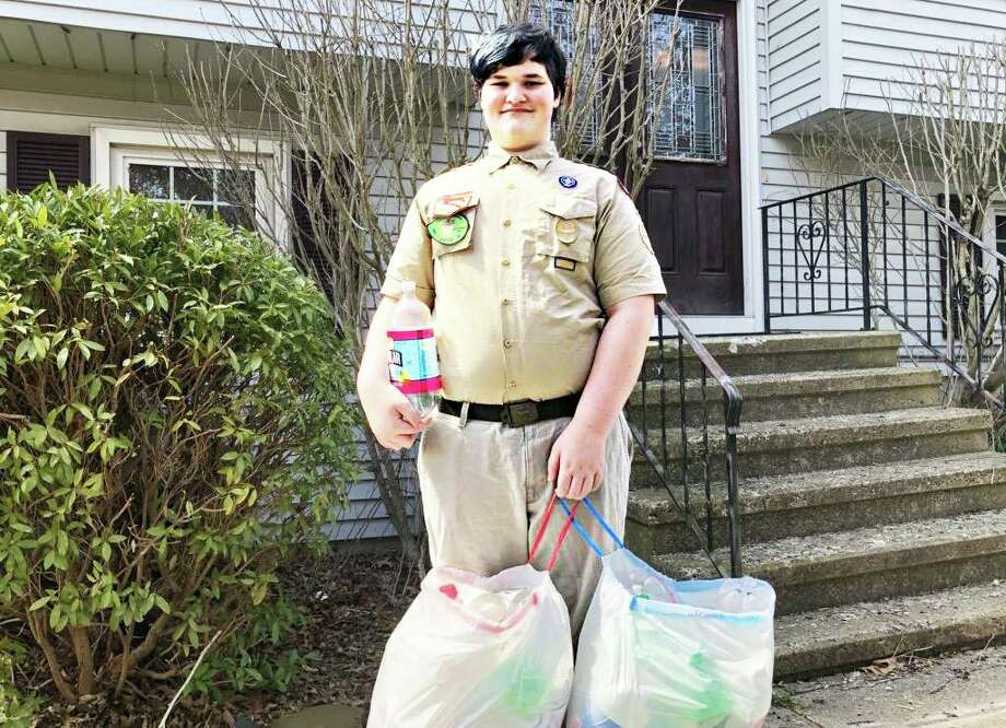 Boy Scout Troop 41 Middletown member Jack Hoover shows off the plastic plastic soda bottles he and others dropped off in Hartford Wednesday. They'll be used for a project that creates face shields out of 2-liter containers. Photo: Contributed Photo
