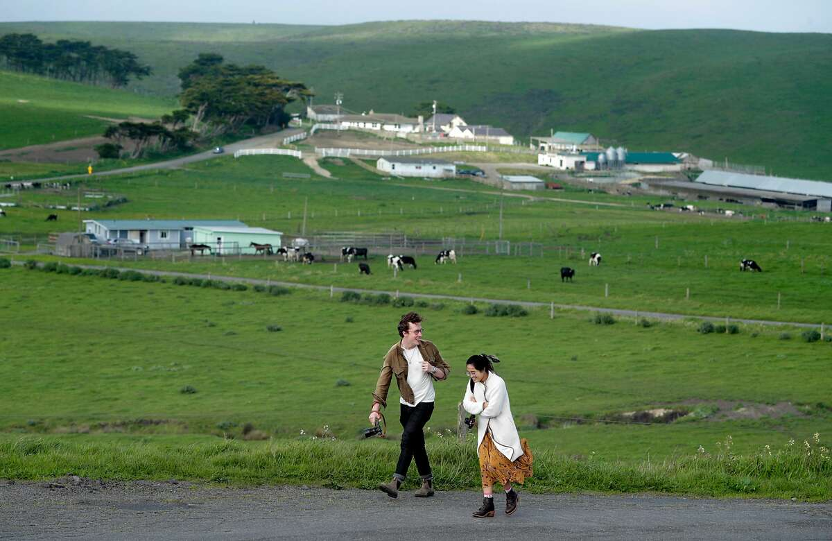 Two visitors walk along Sir Francisco Drake Boulevard with a dairy in the background at the Point Reyes National Seashore. Dairy and ranching operations may continue under the parks' new management plan.