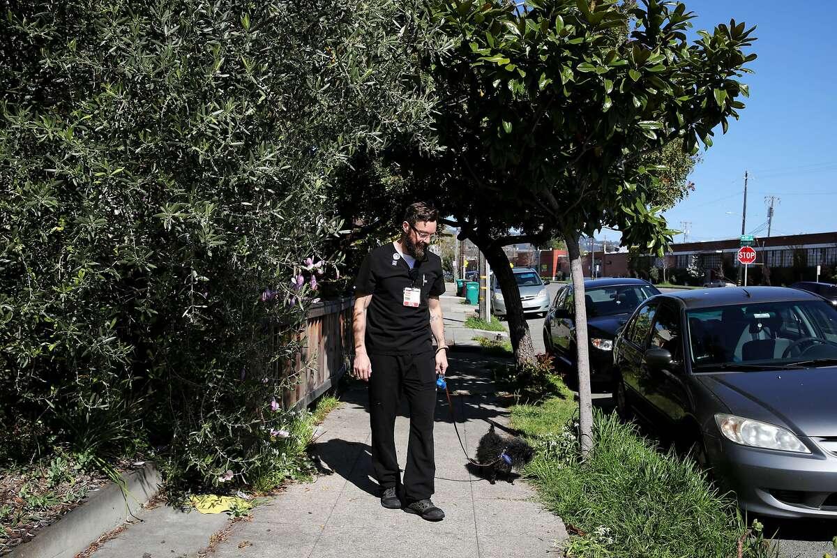 John Pearson, 40, an emergency department clinical nurse II, Alameda Health System, walks his dog, Stella, on Wednesday, April 1, 2020, in Oakland, Calif.