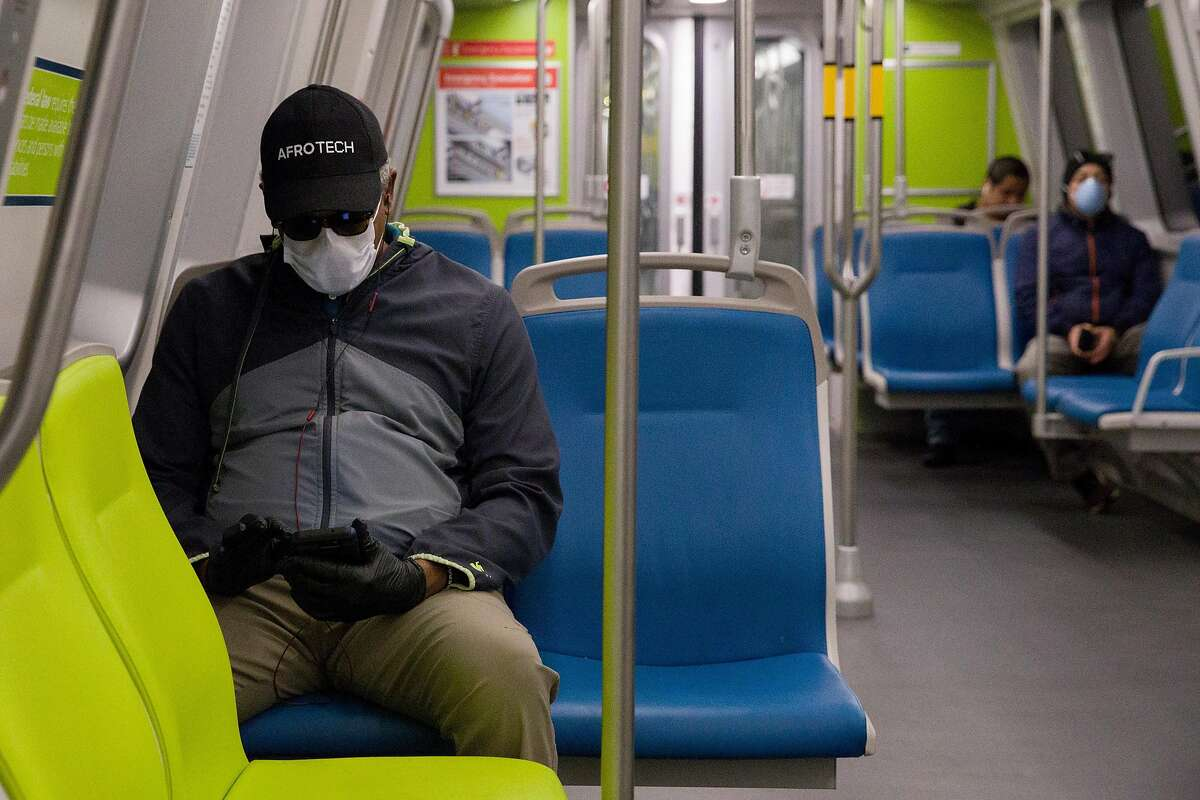 A man wears a mask and gloves while socially distancing from other riders on a Richmond-bound train from 19th Street BART Station in Oakland, Calif. Friday, April 3, 2020. Although BART has seen a drastic decline in ridership, those who still use their services have been seen wearing protective gear and practicing social distancing.