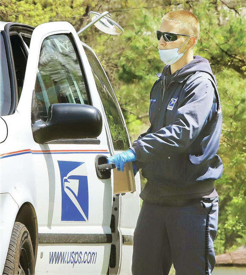 A U.S. Postal Service letter carrier, wearing gloves and a face mask, returns to his vehicle after delivering an area of Alby Street in Alton. The USPS has taken steps to reduce the chance of spreading COVID-19 through interactions; officials emphasize there is no evidence COVID-19 can be spread through pieces of mail.