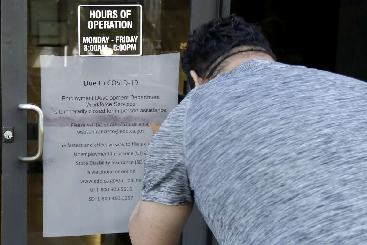A man takes a photo of a sign advising that the Employment Development Department is closed due to coronavirus concerns, in San Francisco on Thursday, March 26, 2020. A record-high number of people applied for unemployment benefits last week as layoffs engulfed the United States in the face of a near-total economic shutdown caused by the coronavirus.