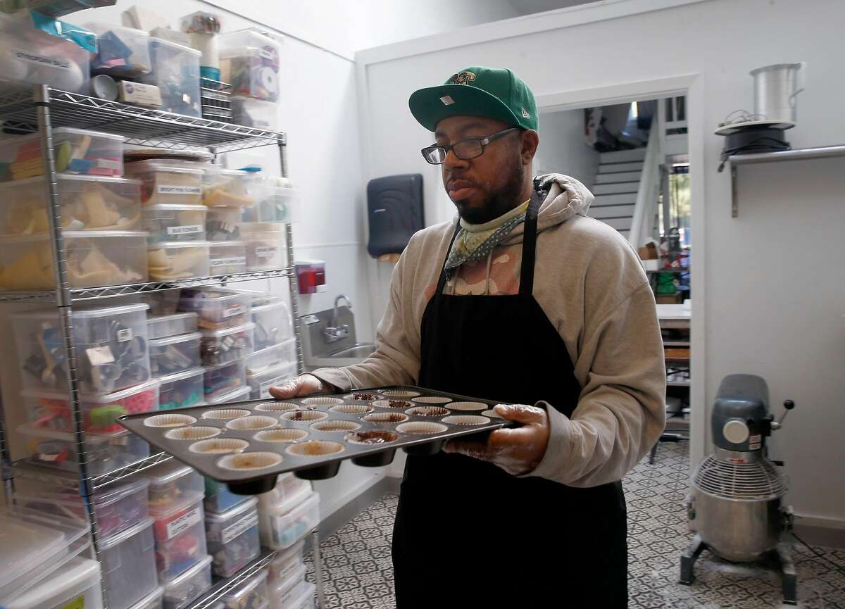 David Benton carries cupcakes to the oven at Sugarsweet Cake and Cookie Studio in Oakland, Calif. on Wednesday, April 15, 2020. Benton's bakery has been limited to pickup and delivery service only during the coronavirus pandemic.