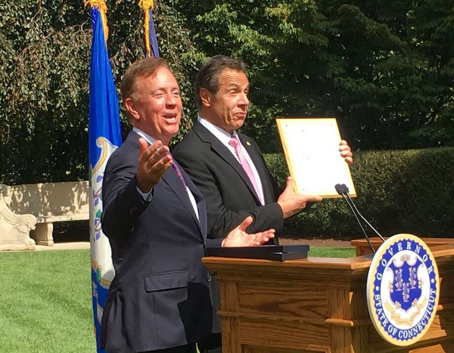 Connecticut Gov. Ned Lamont, left, and New York Gov. Andrew Cuomo share a laugh after Lamont gave Cuomo a mounted Connecticut fishing license at the governor's mansion in Hartford, Sept. 25, 2019. Photo: Dan Haar /Hearst Connecticut Media
