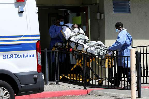 Employees with Falcon Critical Care Transport remove a patient from  Gateway Care and Rehabilitation on Wednesday, April 15, 2020, in Hayward, Calif. The facility currently has eleven COVID-19 related deaths with dozens of staff members and patients infected with the novel coronavirus.