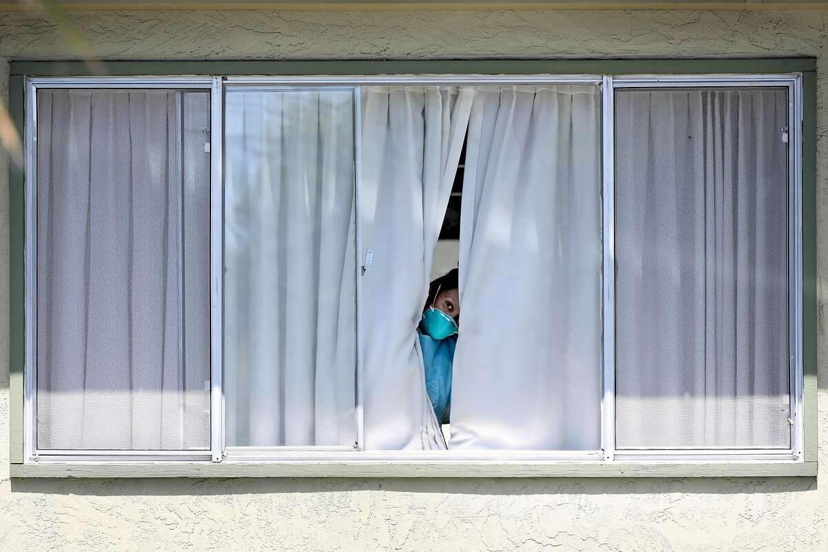 An employee wearing protective gear peeks from a window after a patient was picked up by Falcon Critical Care Transport at Gateway Care and Rehabilitation on Wednesday, April 15, 2020, in Hayward, Calif. The facility currently has eleven COVID-19 related deaths with dozens of staff members and patients infected with the novel coronavirus.