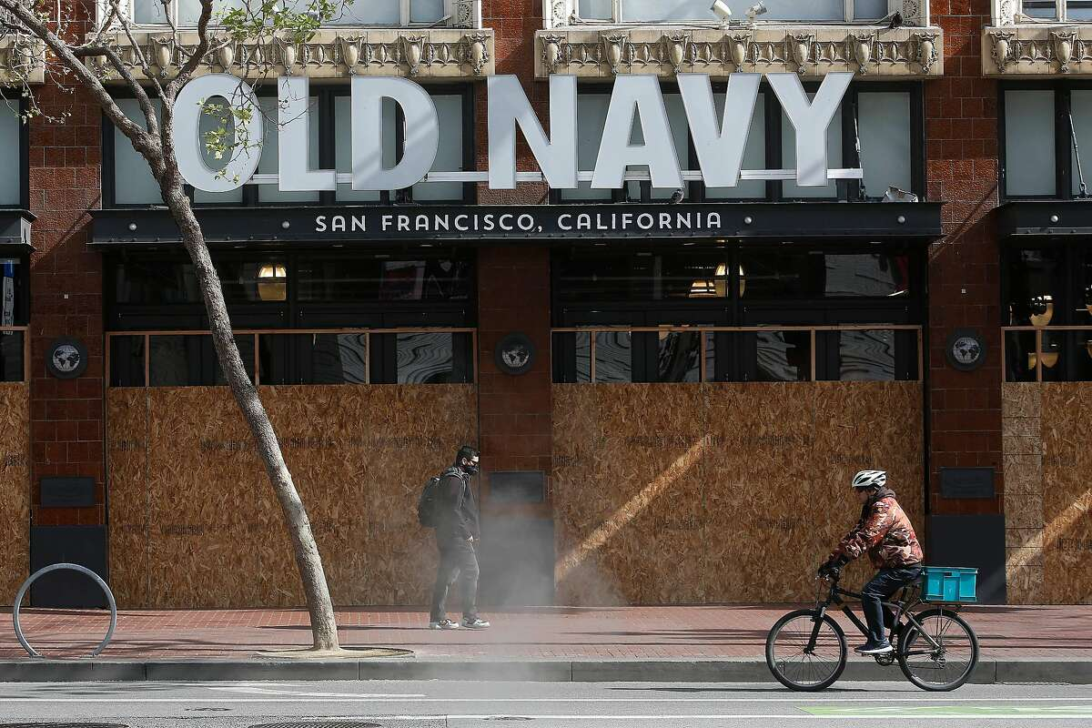 A pedestrian walks past a boarded up Old Navy store on Market Street as a bicyclist rides past on Friday, March 27, 2020 in San Francisco, Calif.
