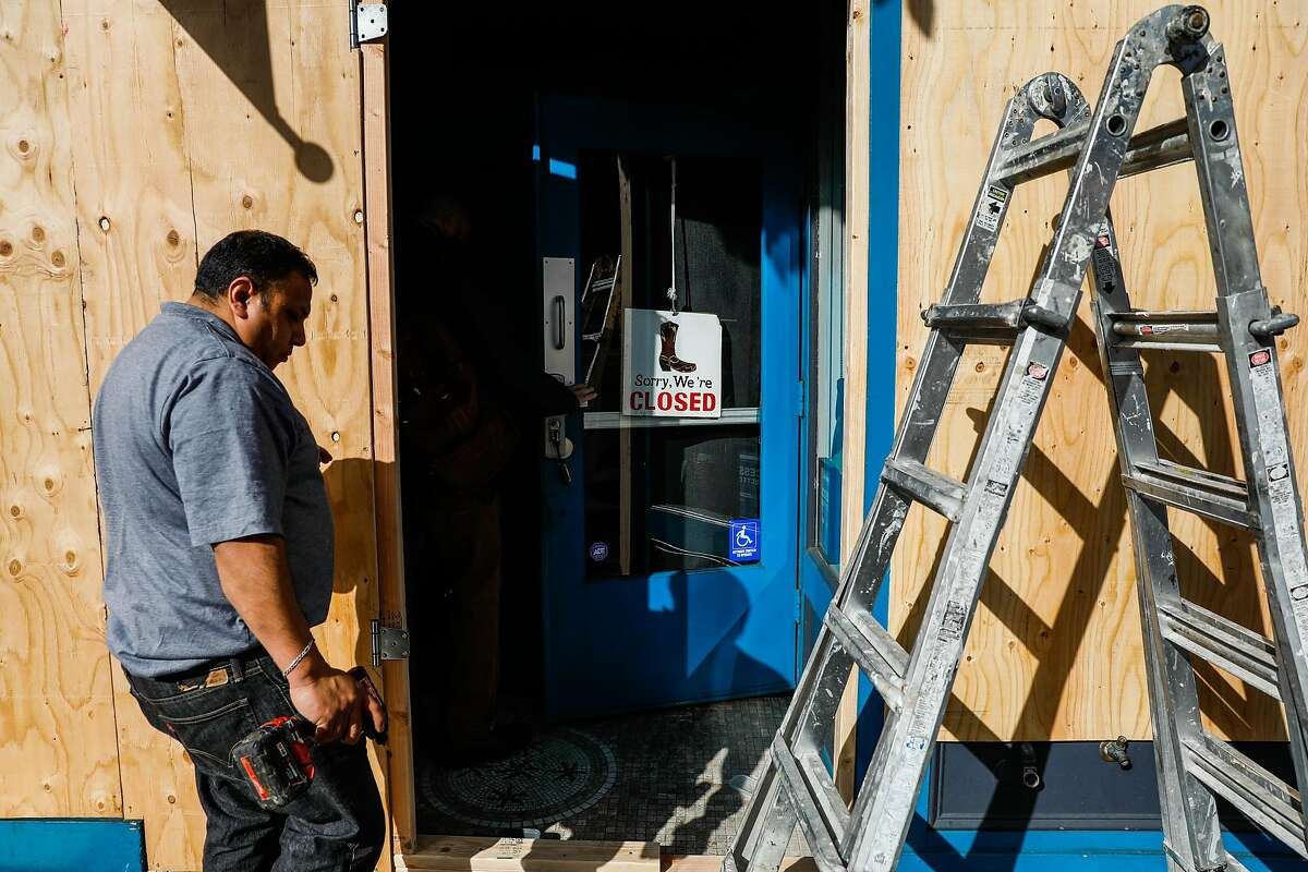 Worker Robert Martinez boards up Lolo restaurant out of fear of break-ins during the citywide lockdown on Valencia Street on Tuesday, March 17, 2020 in San Francisco, California.