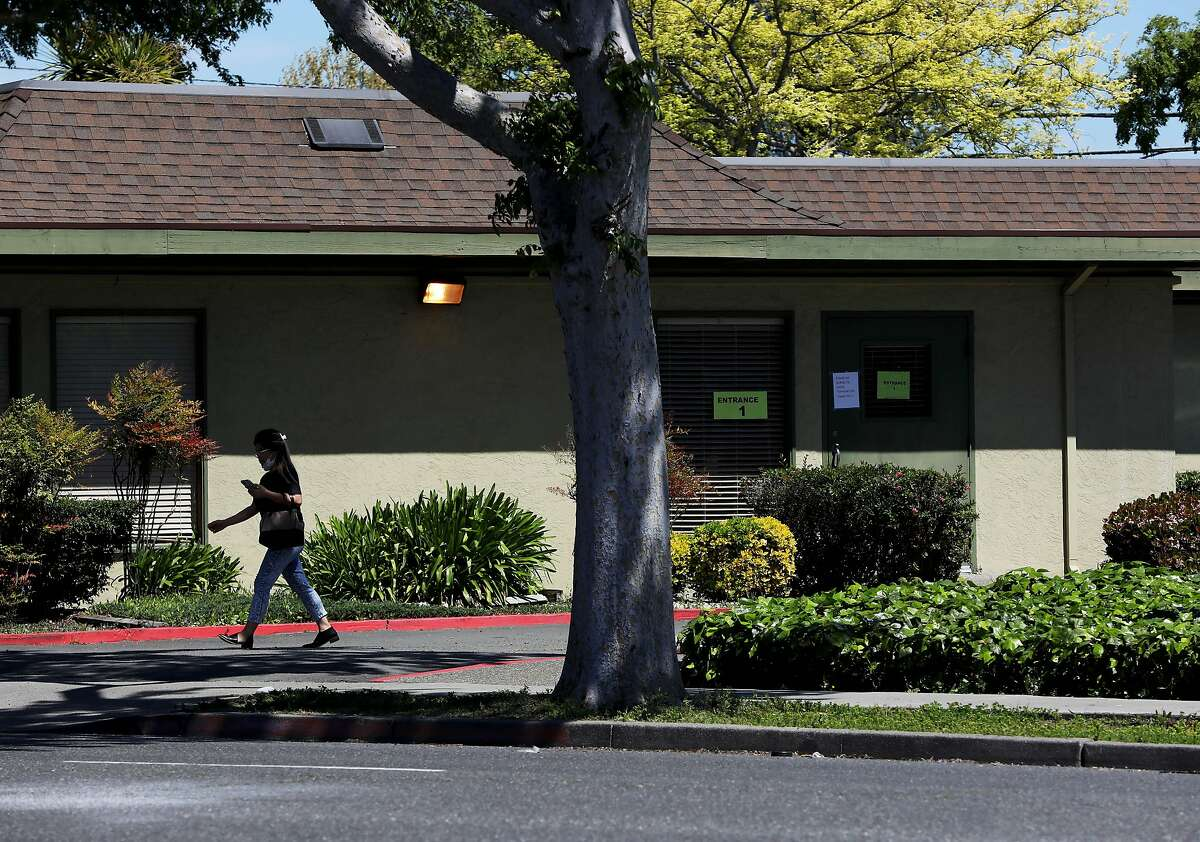A woman leaves the Gateway Care and Rehabilitation Center, located at 26660 Patrick Ave., on Wednesday, April 15, 2020, in Hayward, Calif. The facility currently has eleven COVID-19 related deaths with dozens of staff members and patients infected with the novel coronavirus.