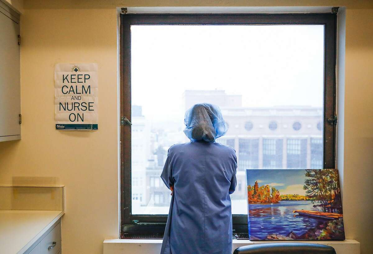 Supervising nurse Regina Truong looks out the window as she takes a break at the Covid-19 floor at Saint Francis Hospital in San Francisco on Monday, April 6, 2020.