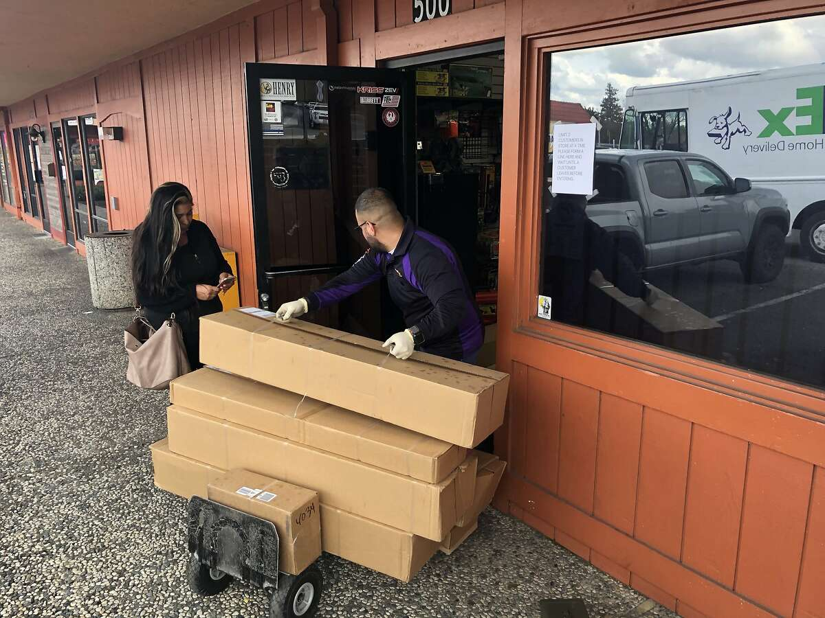 A FedEx employee delivers supplies to Marin Firearms in Novato on Tuesday afternoon as Sharon Femenia, 49, a Novato gun collector, waits in line to buy ammunition for her family's handguns and rifles.