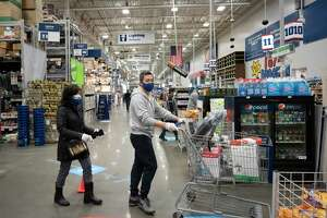 FILE - In this April 3, 2020 file photo, Lowe's customers wear gloves and masks as they shop during the coronavirus pandemic in New York. U.S. retail sales plummeted 8.7% in March, a record drop as the viral outbreak closed down thousands of stores and shoppers stayed home. Sales fell sharply across many categories: Auto sales fell 25.6%, while clothing store sales collapsed, dropping 50.5%. (AP Photo/Mark Lennihan, File)