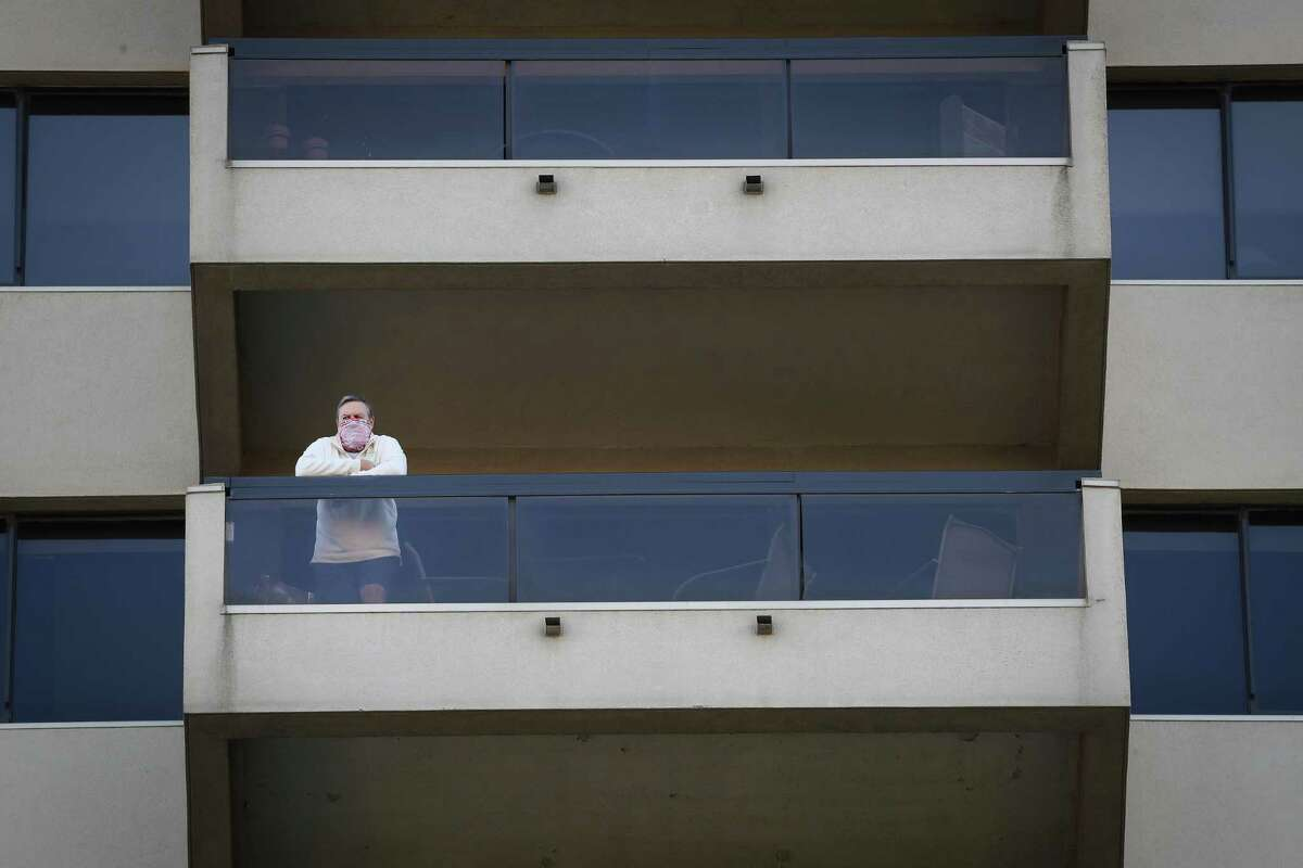 Bill Turney, a 72-year-old resident, stands on his balcony of the Park Square Condominiums Tuesday, April 14, 2020, in Houston.