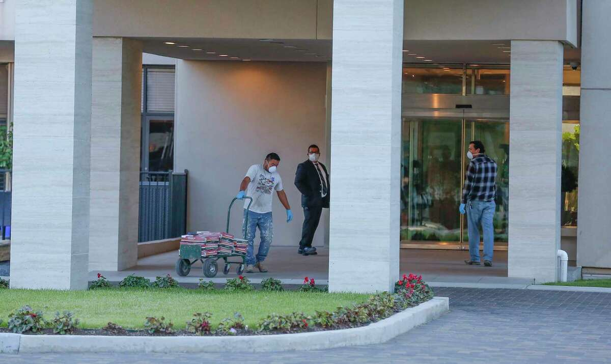 Workers enter the Park Square Condominiums Tuesday, April 14, 2020, in Houston.