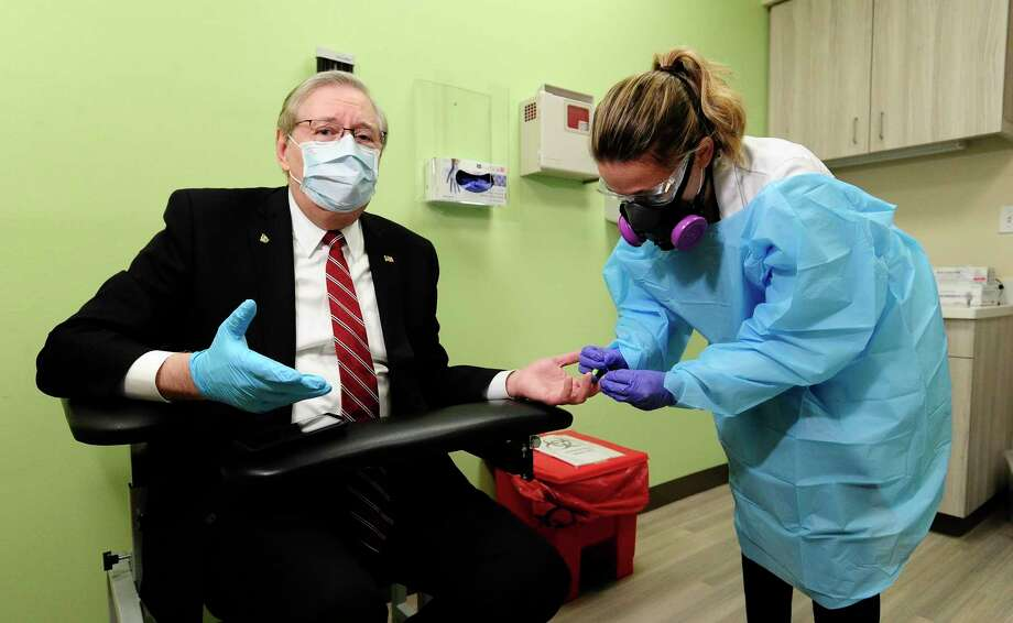 Mayor David Martin, along with key Public Safety personnel (Police Chief, Fire Chief, Director of Health) demonstrate a finger-prick test used to identify if an individual is likely to have COVID-19 without utilizing high-in-demand COVID-19 test kits. Physician Assistant Laura Kragt of Docs Urgent Care in Stamford, Conn., on April 9, 2020, performed a test on Mayor Martin, who was told within minutes of the test that he had tested negative to the virus. Martin is pushing to use this testing method on Stamford's first responders twice a month to help indicate whether they have been exposed to COVID-19 virus. a new Fingerprick test for the COVID-19 virus, that they are hoping to test all First Responders twice a month with. This test only indicates whether you are positive or negative to carrying the antibodies of COVID, a second test would be used (Nose Swab) to confirm if the individual was infected with COVID-19, requiring isolation. Photo: Matthew Brown / Hearst Connecticut Media / Stamford Advocate