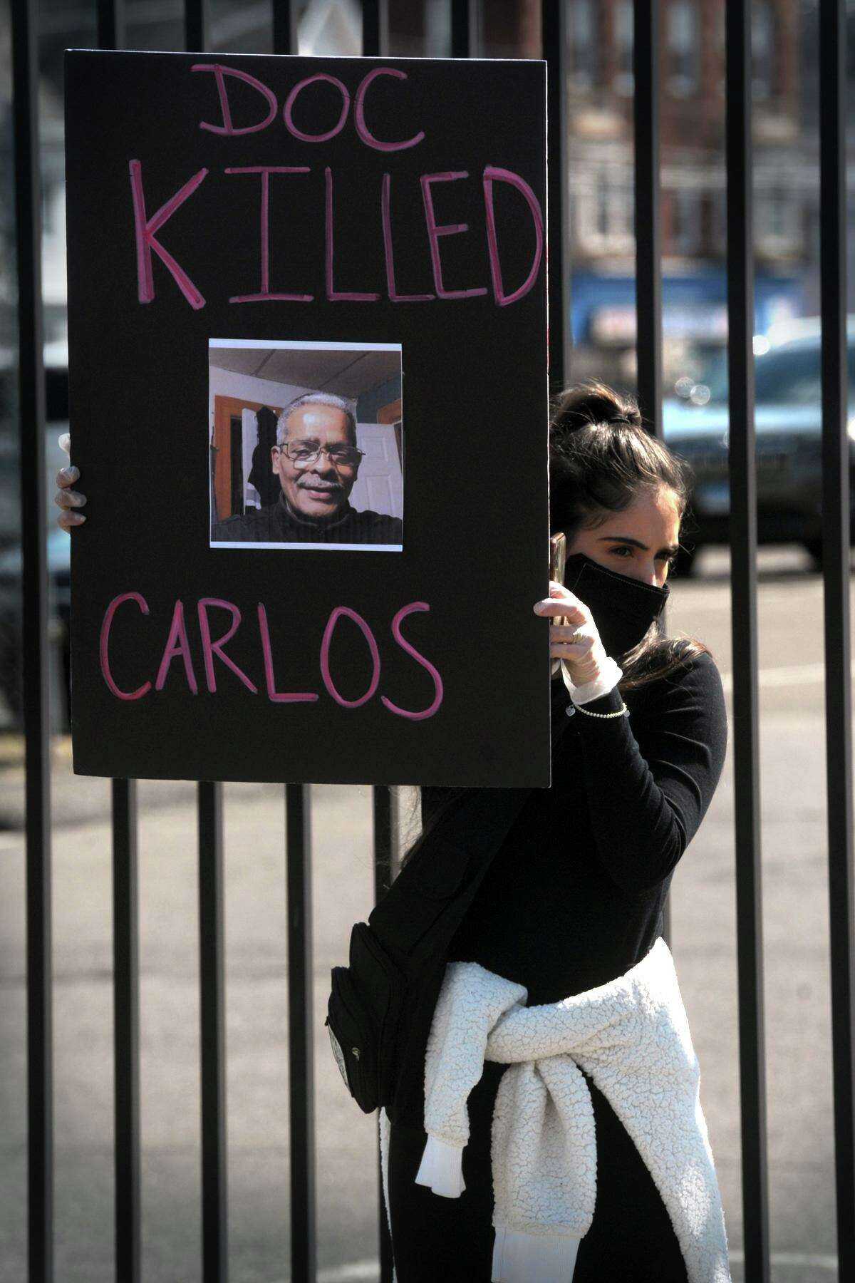 A woman holds a poster with the image of Carlos DeLeon during Wednesday's protest. DeLeon died in a state prison Monday after contracting coronavirus.