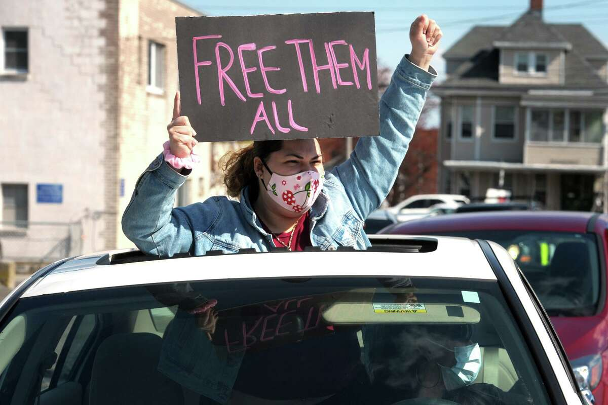 A woman gestures through the sunroof of a passing car during a protest outside the Bridgeport Correctional Center, in Bridgeport, Conn. April 15, 2020.