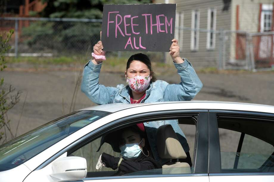A woman gestures through the sunroof of a passing car during a protest outside the Bridgeport Correctional Center, in Bridgeport, Conn. April 15, 2020. Photo: Ned Gerard / Hearst Connecticut Media / Connecticut Post