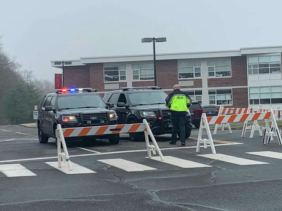 New Canaan Police restrict access to the parking lot at Saxe Middle School to those who have been given an appointment with Murphy Medical Associates to be tested for the disease COVID-19 recently. The coronavirus causes the disease COVID-19. The death toll from the coronavirus increased to 18 on Thursday, April 16, 2020, days after fields, and parks closed for at least a month to stop its spread. Photo: John Kovach / Hearst Connecticut Media / New Canaan Advertiser