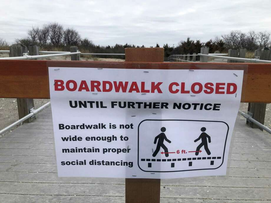 A sign announces the closure of the boardwalk at Hammonasset Beach State Park in Madison, Conn. Jennifer Simpson, director of the Madison Historical Society, took the photo to record what life was like in town during the coronavirus pandemic in the spring of 2020. Photo: Contributed Photo / Jennifer Simpson