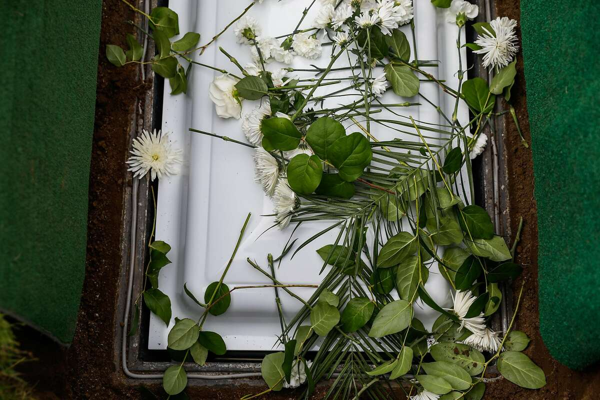 Flowers cover the casket of Tessie Henry who died of Covid-19 at the age of 83 is buried on Wednesday, April 8, 2020 in Colma, California.