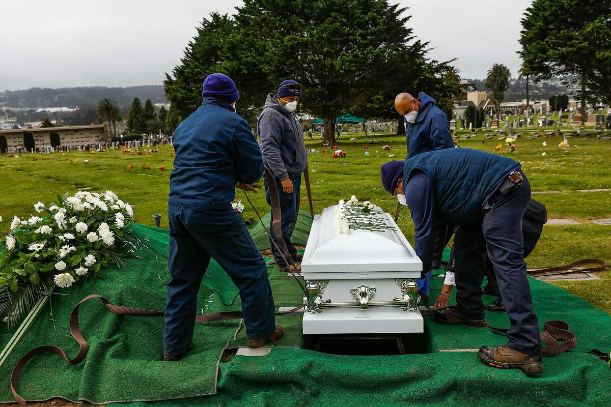 Cemetery workers bury Tessie Henry who died of Covid-19 at the age of 83 is buried on Wednesday, April 8, 2020 in Colma, California.