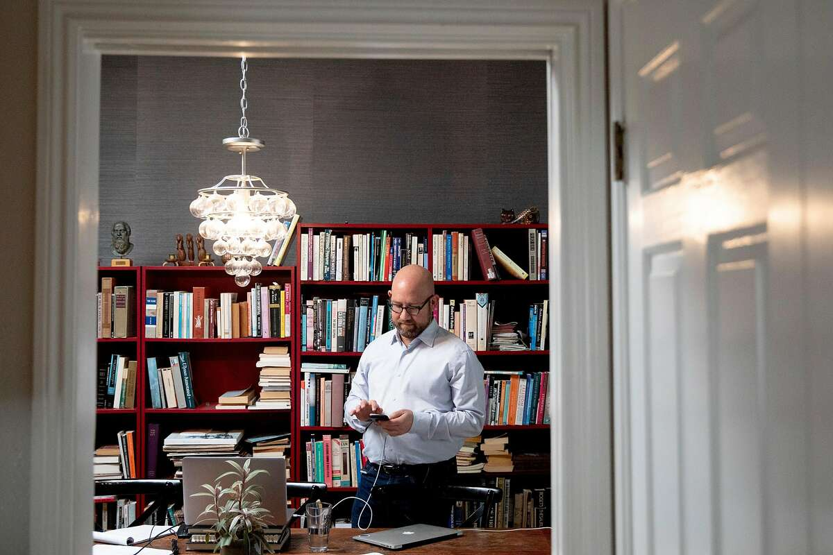 San Francisco District 8 Supervisor Rafael Mandelman checks his phone while working from his home in San Francisco, Calif. Thursday, April 9, 2020.in San Francisco, Calif. Thursday, April 9, 2020.