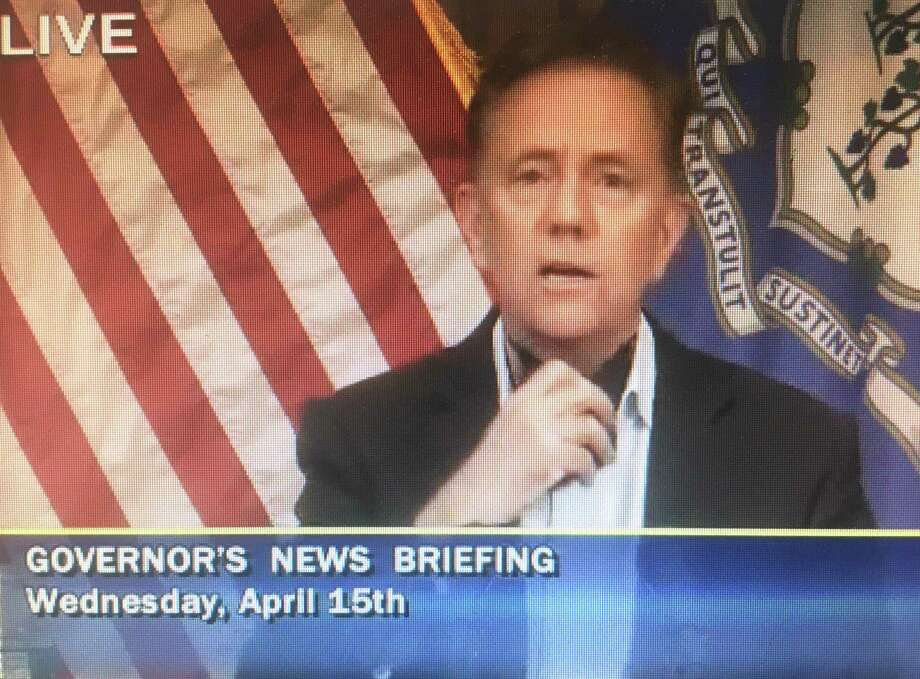 Gov. Ned Lamont didn't put on his black mask in a news briefing where he announced mandatory masks, but he had it around his neck and pointed to it. Photo: CT-N Network Feed