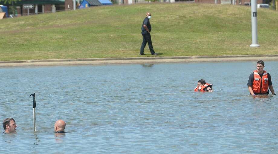 Emergency crews and the dive team work the scene at the Lake at the Event Centre, where a child and adult, who is tentatively identified as the boy's mother, drowned Wednesday. According to Haley Morrow, initial reports indicate the boy fell into the water, and the mother then went in after him. The mother was revived by paramedics as the dive team continued scouring the pond for the three-year-old boy, who was later brought up by a diver. Crews continued CPR on the little boy, who was also taken to an ambulance for transport to the hospital. The boy was later reported dead and the mother in critical condition. Photo taken Tuesday, April 14, 2020 Kim Brent/The Enterprise Photo: Kim Brent/The Enterprise