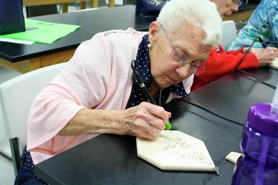 Betty Anderson carefully traces a cardinal with a wood burning tool during Senior Enrichment Day in 2018. This year's event has been canceled because of coronavirus concerns. (Pioneer file photo)