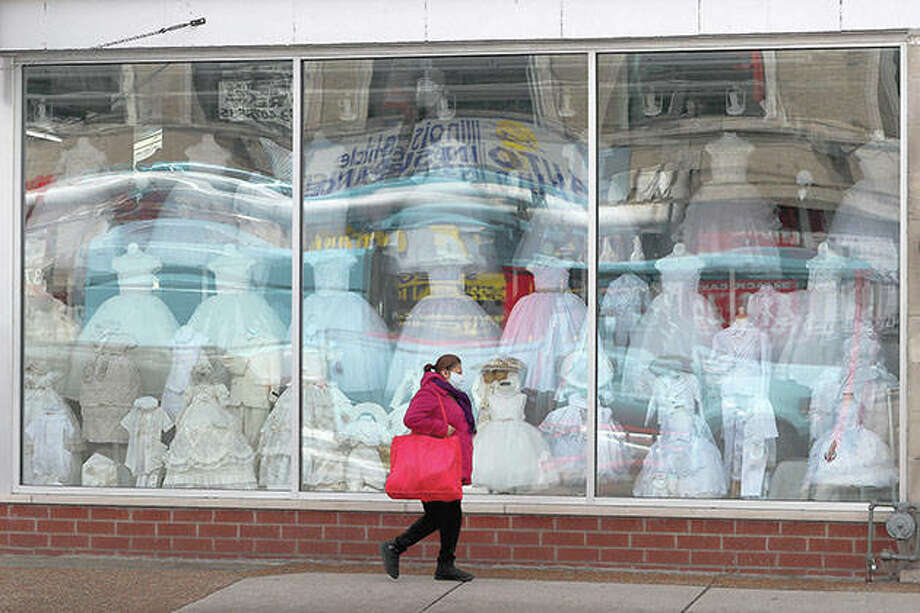 A woman wearing a protective mask walks Wednesday past a closed children's clothing store in Chicago. The first U.S. economic indicators to capture the devastation brought on by the pandemic have begun to arrive, showing a plunge in retail sales exceeding what happened during the economic crisis a decade ago. Photo: Charles Rex Arbogast | AP