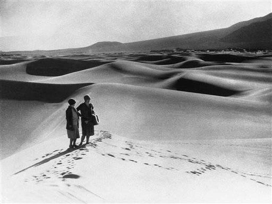 Two women stand near Stove Pipe Wells in the vast sand dunes of Death Valley, California, USA around April 16, 1930. (AP Photo)