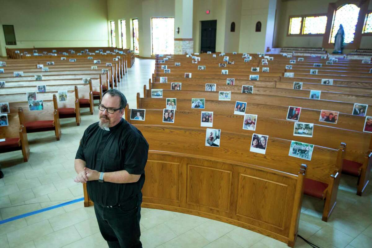 The Rev. Sean Horrigan, parish priest, stands in the sanctuary at Christ the Redeemer Catholic Church in front of photos of parishioners that are taped to the pews, which are part of virtual masses at the church, on Friday, April 10, 2020, in Houston. The coronavirus pandemic has shut down most religious services throughout the country and many churches are offering services through social media and video conferencing.