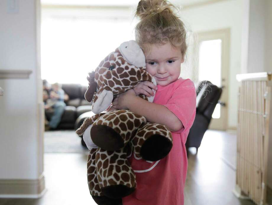 A child hugs a stuffy she received years ago on a trip to the zoo with her mom.  With children staying at home now, and families facing increased stress, the potential for child abuse is high. There are still many ways to support families and report potential abuse. Photo: Elizabeth Conley /Staff Photographer / © 2019 Houston Chronicle USE ONLY IN DO NO HARM: This image may not be resold. No archive. No standalone internet. No social med