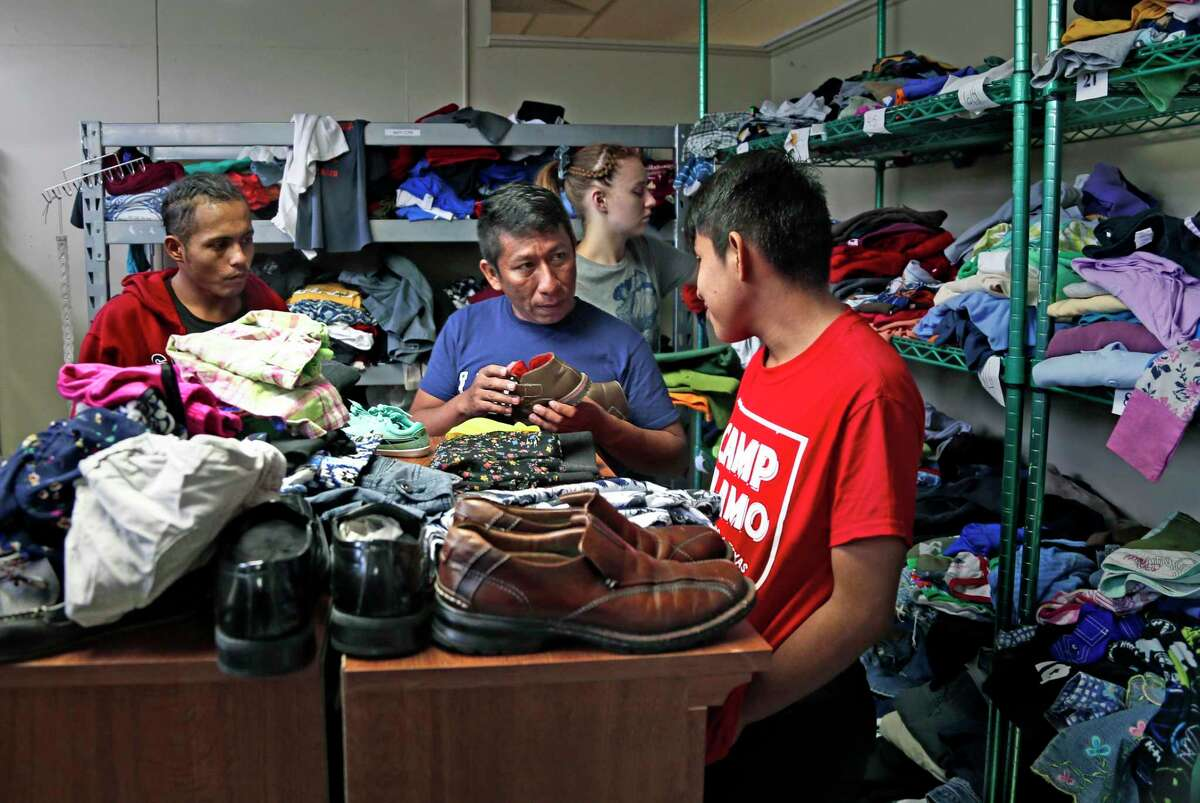 South Texas groups are trying to help immigrant families amid the coronavirus outbreak. Here, migrants look for clothes at the Guadalupe Community Center, provided by Catholic Charities .