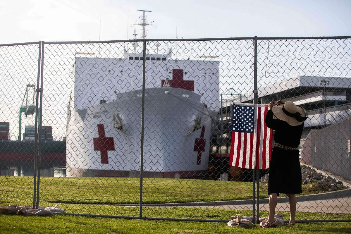A woman hangs a US flag in a fence in front of the US Navy Hospital ship Mercy on March 28, 2020 at the Port of Los Angeles in the city of San Pedro to help local hospitals amid the growing Coronavirus crises in Los Angeles, California. - The ship hold 1000 beds which will be used to treat non-coronavirus patients. (Photo by Apu GOMES / AFP) (Photo by APU GOMES/AFP via Getty Images)