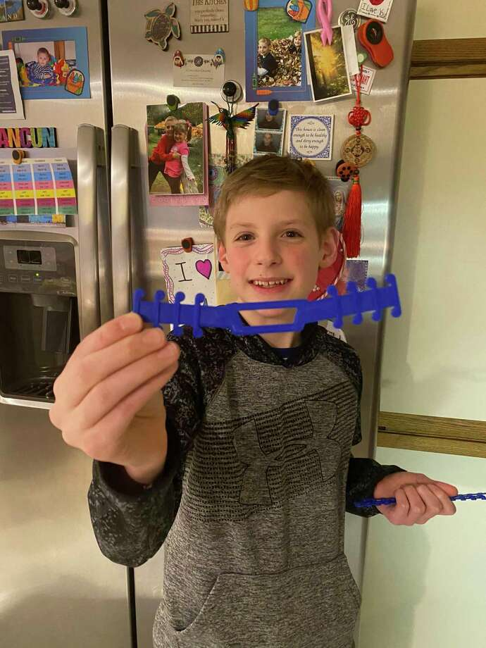 Nick Smith of Midland holds up one of the face mask strap holders he created with his 3D printer. (Photo provided/Aida Smith)