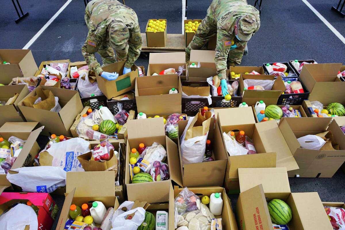 Members of the New York National Guard Bravo Company 427th BSB, out of Fort Drum, place oranges into food boxes that will be distributed to those in need during a mass food distribution on Thursday, April 16, 2020, in Albany, N.Y. The event is part of the Catholic Charities?• mobile outreach program. Catholic Charities teamed up with the Regional Food Bank to get food to those in need in the City of Albany. (Paul Buckowski/Times Union)