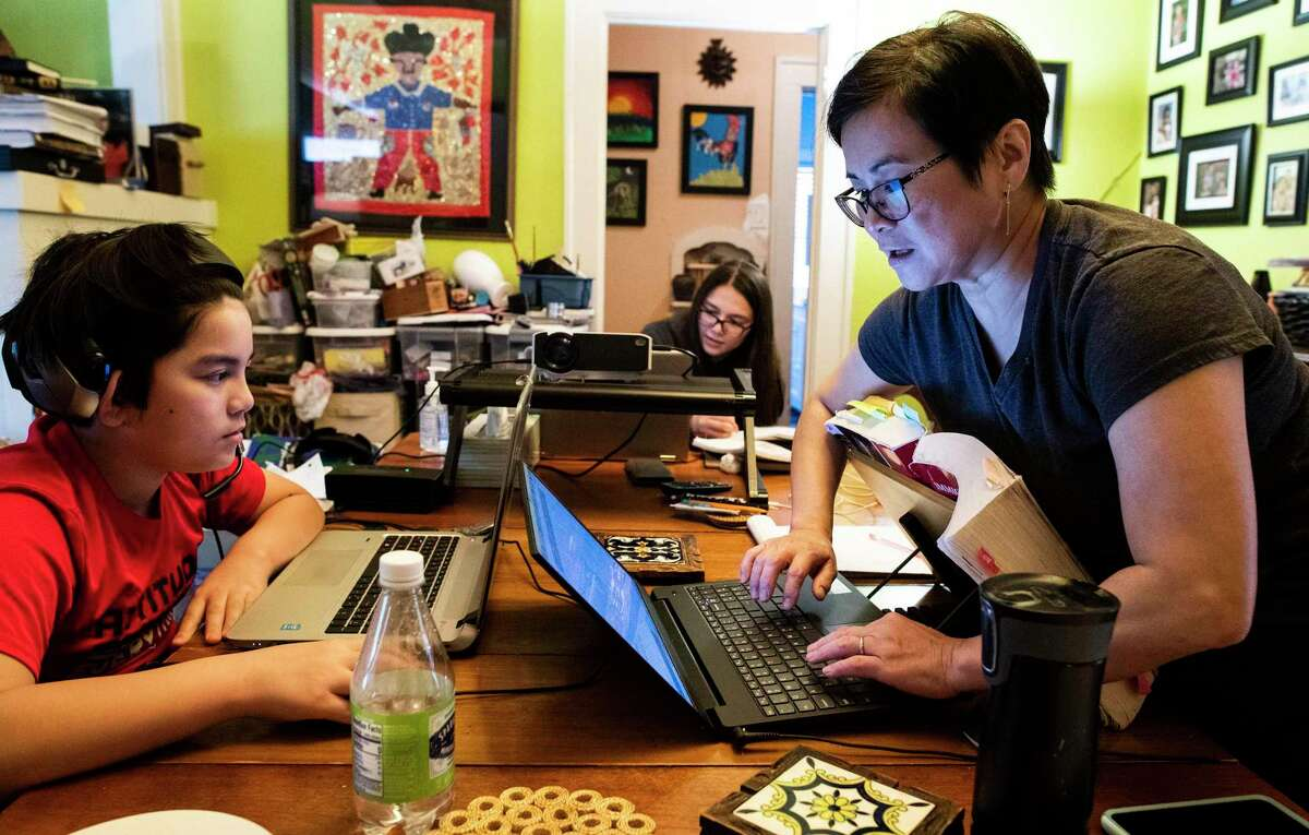 """Analisa Nazareno, a San Antonio immigration lawyer, sets up her computer on the family's dining room table alongside her children, Nico, left, and Mia, in background. She said she and her husband, Richard Milk, have """"sheltered"""" their two children, Mia, 15 and Nico, 11. Neither has cellphones, and the couple limit the amount of TV they watch."""