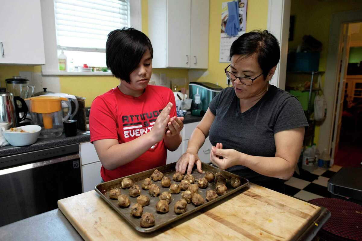 Analisa Nazareno and her son, Nico, make cookies in their family's home. Everyone is able to cook - even if it's just pouring a bowl of Rice Krispies and milk.