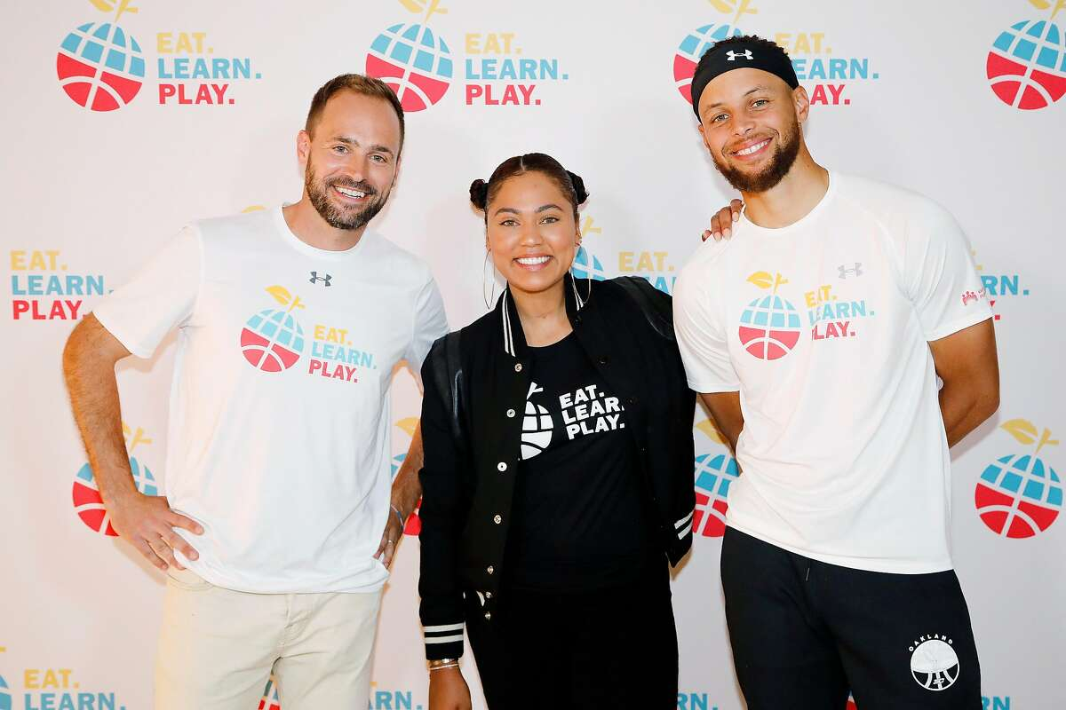OAKLAND, CALIFORNIA - JULY 18: (L-R) Chris Helfrich, Ayesha Curry and Stephen Curry are seen at the launch of Eat. Learn. Play. Foundation on July 18, 2019 in Oakland, California. (Photo by Kimberly White/Getty Images for for Eat. Learn. Play.)