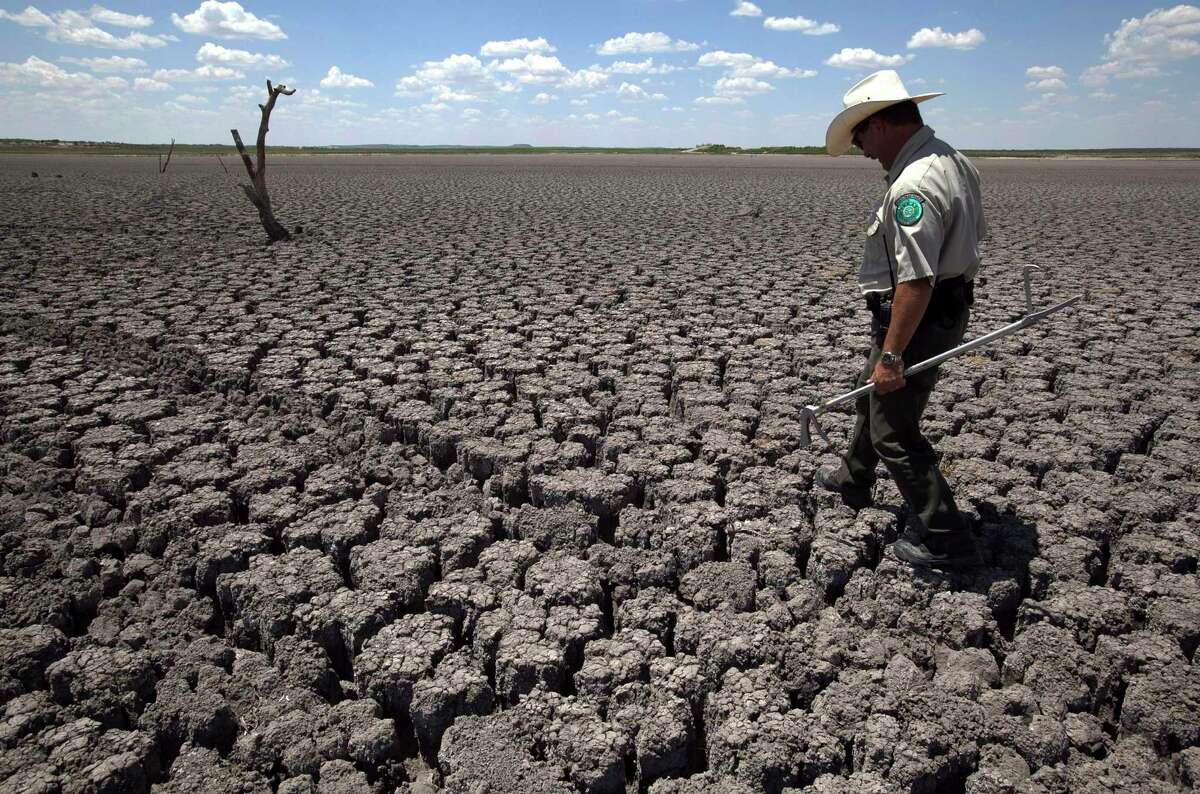 Texas State Park police officer Thomas Bigham walks across the cracked lake bed of O.C. Fisher Lake in San Angelo in this 2011 photo. The American West is well on its way into one of the worst mega-droughts on record, a new study warns.