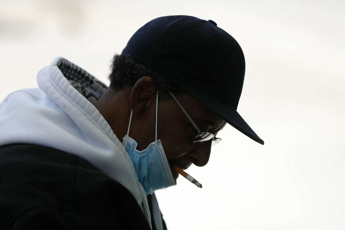A man smokes a cigarette while wearing a protective mask while waiting for a bus in Detroit, Wednesday, April 8, 2020. Detroit buses will have surgical masks available to riders starting Wednesday, a new precaution the city is taking from the new coronavirus COVID-19. (AP Photo/Paul Sancya)