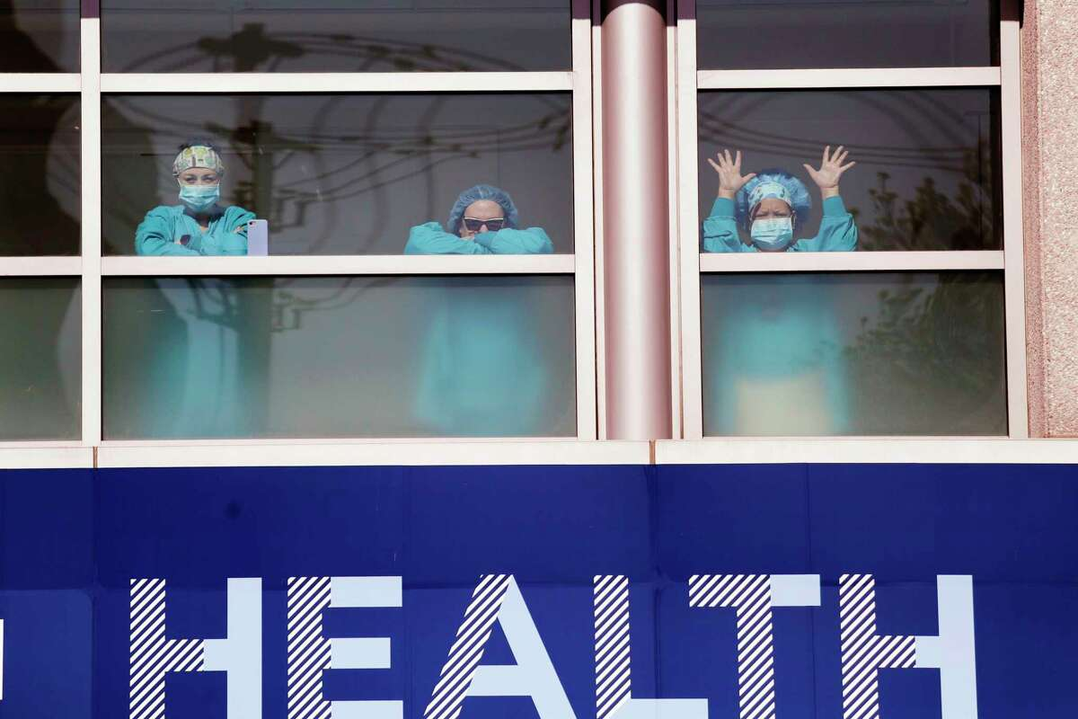 Swedish Medical Center health care workers battling the coronavirus outbreak look on from inside the hospital as first responders gathered outside in support of them Thursday, April 16, 2020, in Seattle. First responders across King County planned to stand outside of 15 hospitals in a show of appreciation for health care workers through the day Thursday.