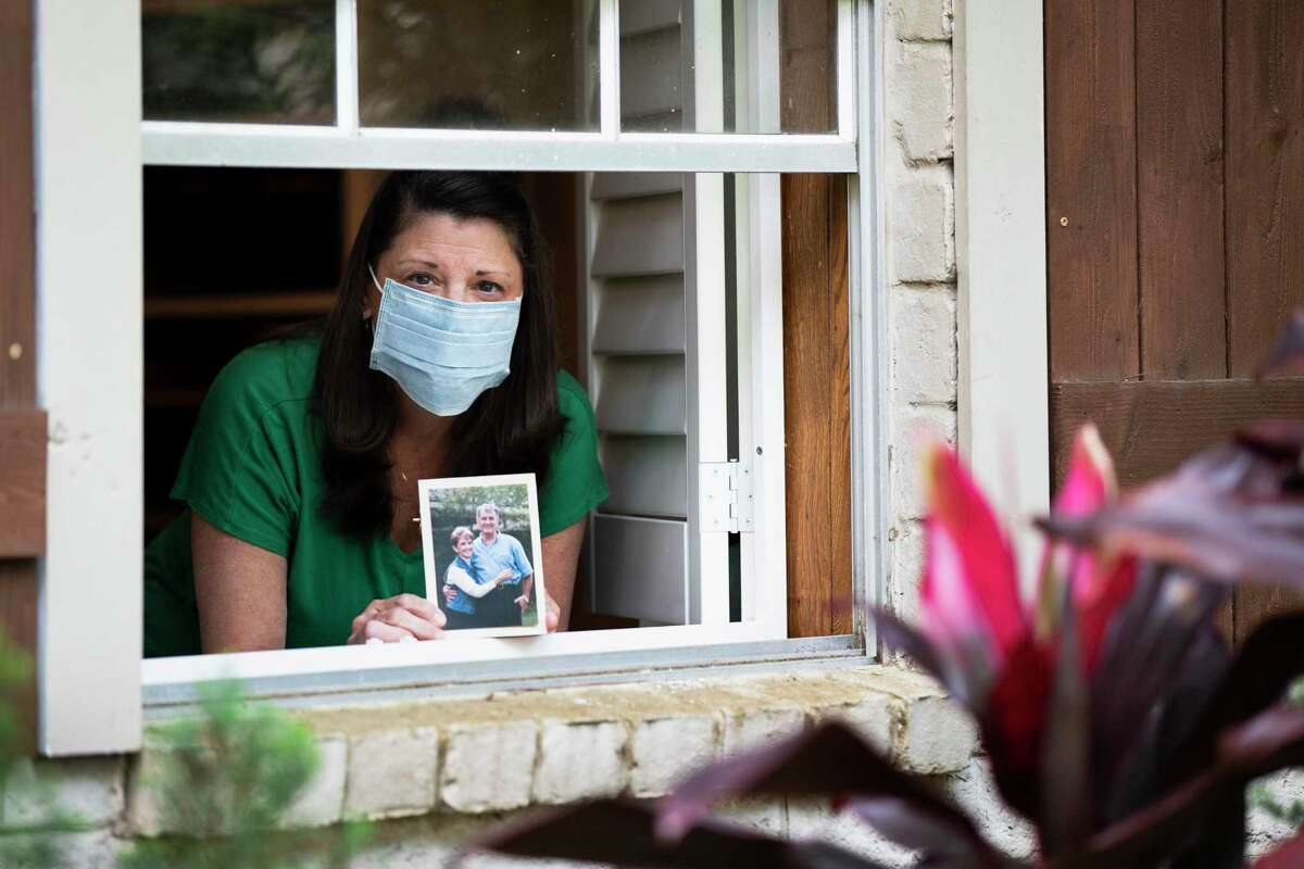 Jina David holds a photograph of her mother and father at her home. David lost her father to COVID-19.